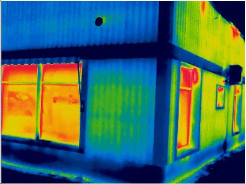 Monivärinen lämpökuva konepajan ulkopuolelta otettuna. Kuvassa näkyy lämpövuotoja.